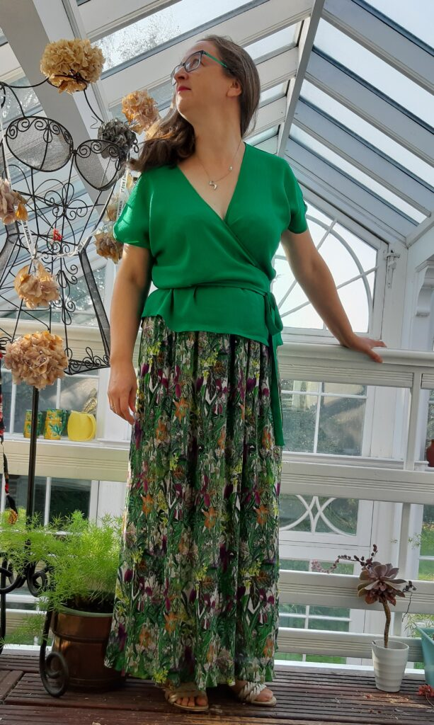 Pippa standing agasint a hand rail wearing a green Zadie wrap top and a maxi skirt